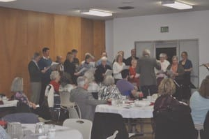 David Boldt directs an alumni choir at the 70th annual Bethel College Fellowship Banquet in Reedley, California.