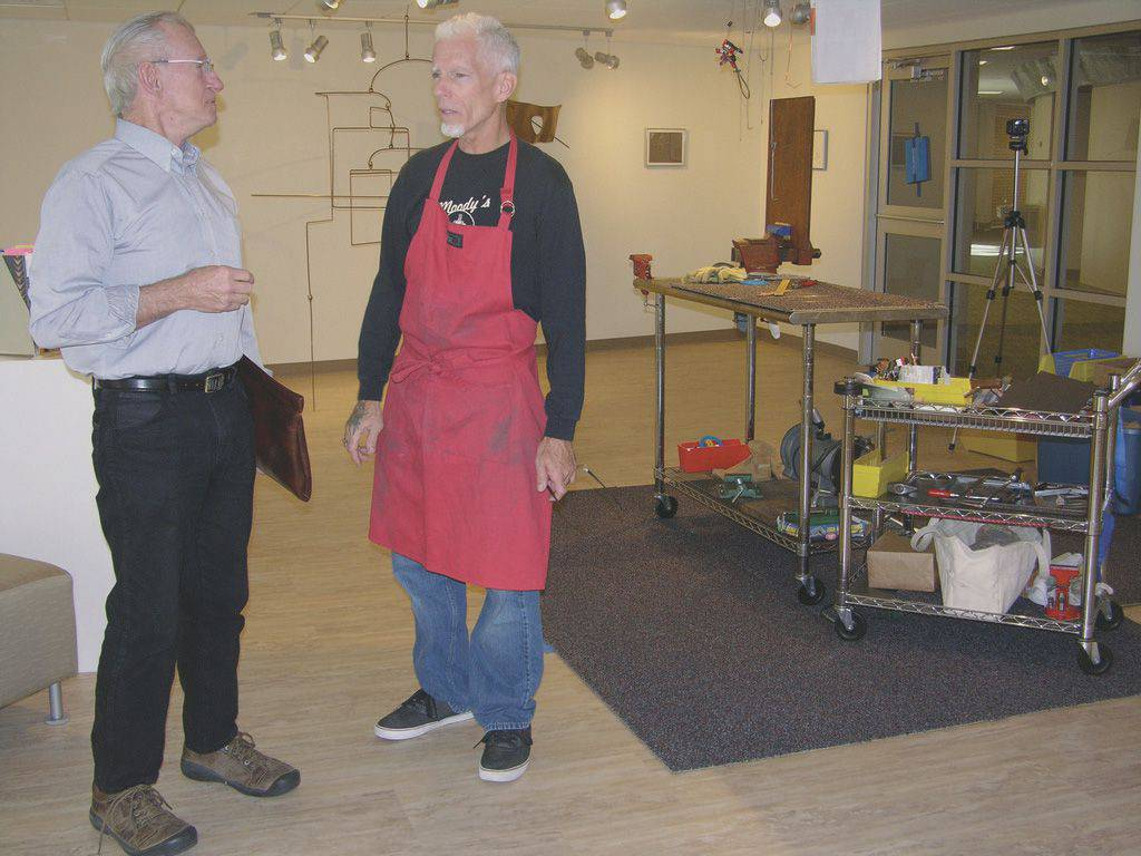 Christopher Gulick, right, visits with Ted Mueller '58 during Gulick's residency last November in the Regier Art Gallery.