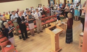 Rachel Unruh '13 leads the singing at the Alumni Weekend worship service and Heritage Roll of Honor memorial service last June.