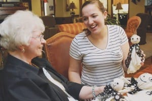 Junior Cayla Lawless makes a new friend while creating Halloween decorations at Kidron-Bethel Village retirement community.