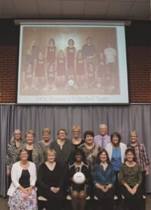 At this year's Hall of Fame Banquet, the 1976 women's volleyball team arranged themselves in the same positions as in the team photo (on screen above their heads) taken 40 years earlier. Front row, from left: Barb Unruh (Beachy), Marcia Kroeker (Miller), Cynthia Alexander (Doyle Perkins), Minnie Wiens and Cynthia Habegger (Loganbill); back: student manager Sheri Unruh (Campos), Annette Stucky (Epp), Sandy Kaufman (Stephenson), Rhonda Wedel, Lori Erb (Thimm), Jill Ewert (Backhus), assistant coach Rich Harder, Margie Harder (Wiens) and coach Barb Graber.