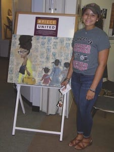Freshman Akiyaa Hagen-Depusoir with the painting she displayed as part of #PieceUnited at Kauffman Museum