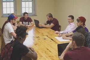 Justin Haflich, left in baseball cap, talks about his cold-calling experience in Professor Bobby Lloyd's Sales class. Continuing clockwise around the table, other members of the class are Ben Carlson, Tyler Kaufman, Jaden Schmidt, Prof. Lloyd, Ryan Ford, Austin Mitchell, Chase Banister and Gary Jolivet.