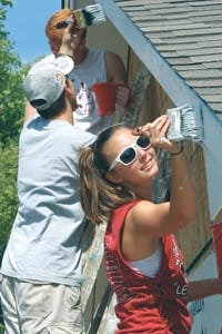From the bottom up, freshmen Georgia Anderson, Jacob Russell and Blayne Stump paint the newest Harvey County Habitat for Humanity house.