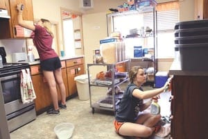 Freshmen Kate Cherveny, left, and Madison Roth deep-clean the kitchen at the Harvey County Homeless Shelter.