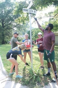 Clockwise from bottom left, freshman Sarah Turner, Professor of Music William Eash, freshman Emma Girton, sophomore Anna Grimsley and junior Dale Kirkland paint a street-sign pole for the City of North Newton.