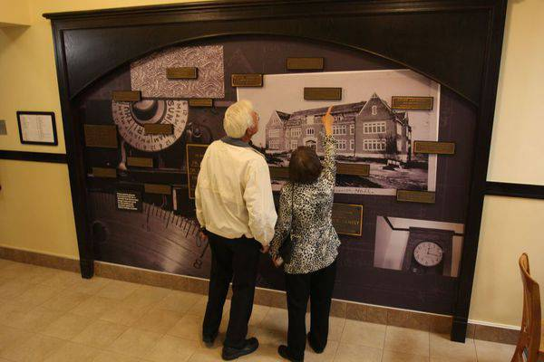 Dorothy '54 and Willis '53 Harder of North Newton admire a mural that includes a photo of Science Hall as a brand-new building ca. 1925, along with the original plates found on or near classroom and office doors that identified donors, and/or those being honored by donations made, to the Science Hall building fund. This mural is in the main entryway; nearby is a new ceramic mural created by Conrad Snider '84 as a commission from the Class of 2008