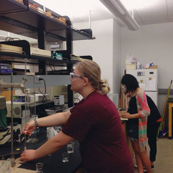 Amber Schmidt-Hayes, left, works at measuring solubility in a chemistry lab at the University of North Texas in Denton, where she is spending the summer in an undergraduate research program sponsored by the National Science Foundation.