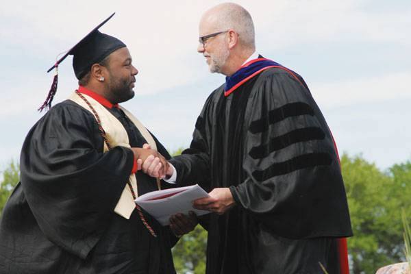 Los Angeles native Sheldon Nunnally, a social work graduate in the Class of 2015, receives congratulations from Brad Born, then vice president for academic affairs.