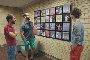 From left, Greg Shelly '11, Wichita, Andy Findley '09, Elkhart, Indiana, and current student Matthew Rodenberg enjoy one of the new photo boards in the Luyken Fine Arts Center, in the 'Theater' area—Andy had found himself in the photo from The Fantasticks on the top, second from right. Photo by Vada Snider.