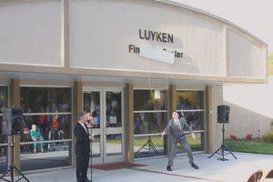 Jacob Miller pulls off the board to reveal the new name of the Luyken Fine Arts Center while President Perry White looks on.  Photo by Vada Snider.