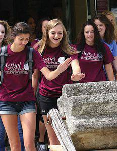 Freshman volleyball players (from left) Caitlin Olson, Tia Goertzen and Mattison Hiebner touch the threshing stone on their way out of the first convoation of the 2013–14 school year.