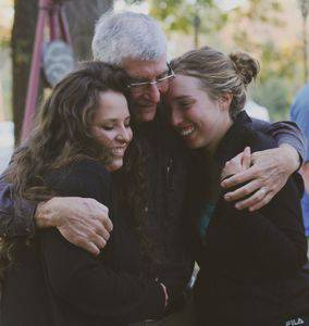 Jerry Weaver '63, Hesston, hugs his granddaughters, Miranda '13, right, and Madelyn .  Photo by Vada Snider.