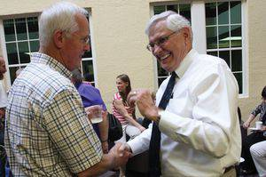 John Sheriff, left, shakes hands with Dale Schrag at a reception for Bethel retirees.  Photo by Vada Snider.