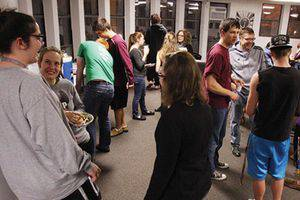 In the left-hand corner, Paige Townley (facing camera) is talking with first-year students Abby Phillips, left, and Heather Eddy. Paige is the resident director for Haury Hall, now a freshman-only residence, and coordinator of the new First-Year Success initiative. The event is a nacho bar that Haury 'hall parents' put on during interterm in the Haury lounge. Gregg Dick '87, seen at right (in gray sweatshirt facing camera) and Ada Schmidt-Tieszen (center background) are two of the 14 hall parents. Photo by Vada Snider.