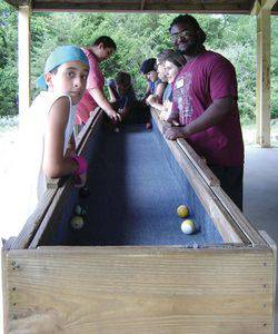 Travon Lewis, right, with Camp Mennoscah campers and a game of carpet ball.