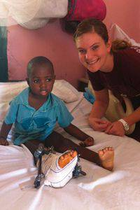 Senior nursing major Erin Hilger in the hospital in Hinche, Haiti, with a boy injured months earlier in a car accident.