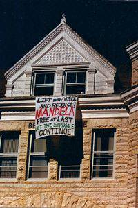 The photo shows a banner made from a sheet, hanging from a third-floor window of the Administration Building. It reads: 'Lift every voice and rejoice! Mandela free at last. Let the struggle continue.'