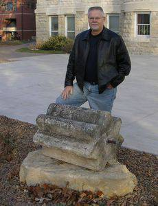 Glen Ediger '75, pictured here with the Ad Building threshing stone, notes that telling the stone's story requires consideration of 'international politics, the opening of the Wild West, the railroad, the search for religious freedom,' plus archaeology, evolution, changes in world food supplies and farming technology, and ancient to modern history. Much like a liberal arts education.